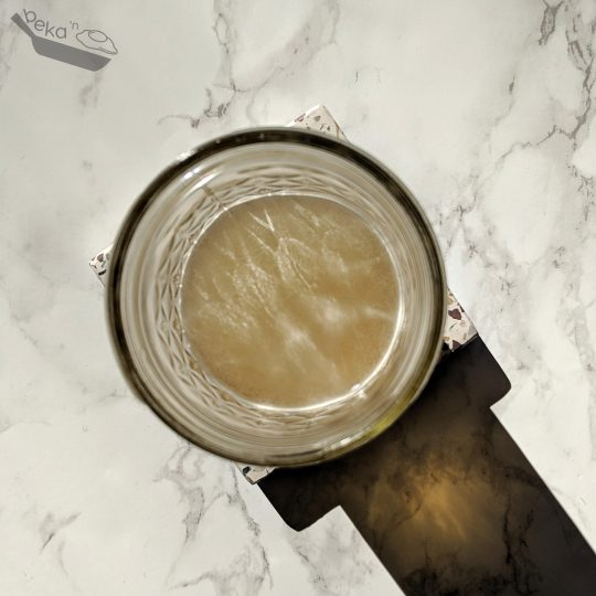 An overhead shot of a crystal cut mason jar on a white marble background. Inside the jar is the homemade workout recovery drink. The light is shining from the top left so there is a big shadow on the bottom right of the image. The squared off part of the shadow is from the stone coaster under the glass, however it is not really visible without this shadow.