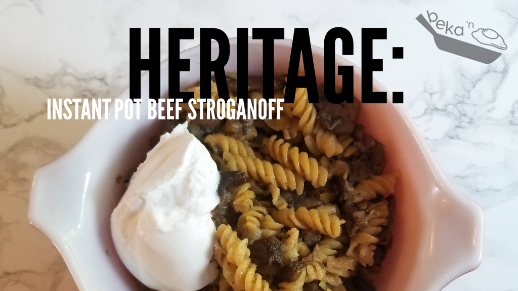 """An overhead shot of pasta, cream, and meat in a vintage pyrex bowl (white on the inside) on a white marble background. Overlay text reads """"Heritage: Instant Pot Beef Stroganoff"""""""