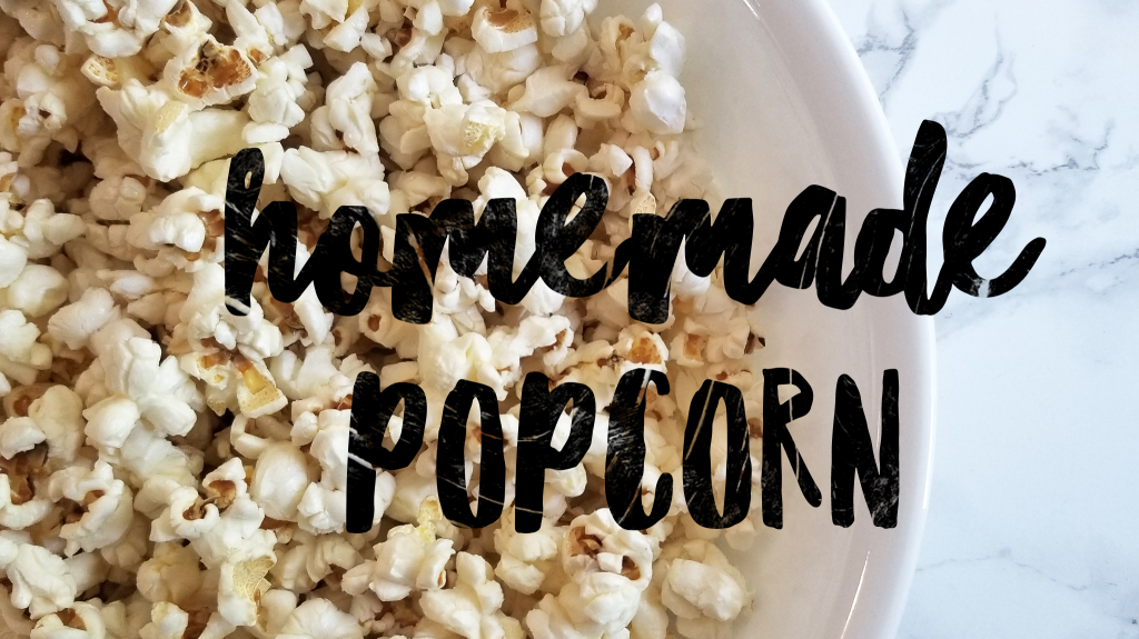 """An overhead close up of homemade popcorn in a large white bowl with a white marble background. An overlay of chunky black text reads """"homemade popcorn'"""