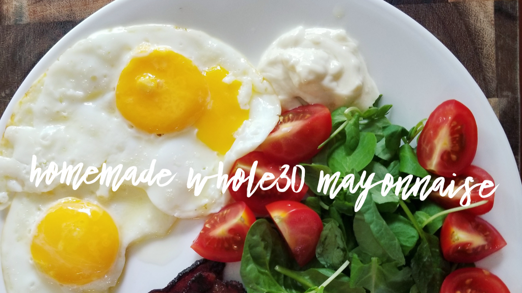 """An overhead image of half a white plate on a wooden checkered pattern cutting board. On the plate are two fried eggs, greens, sliced tomatoes, and mayonnaise. White cursive text overlay reads """"Homemade Whole30 Mayonnaise"""""""
