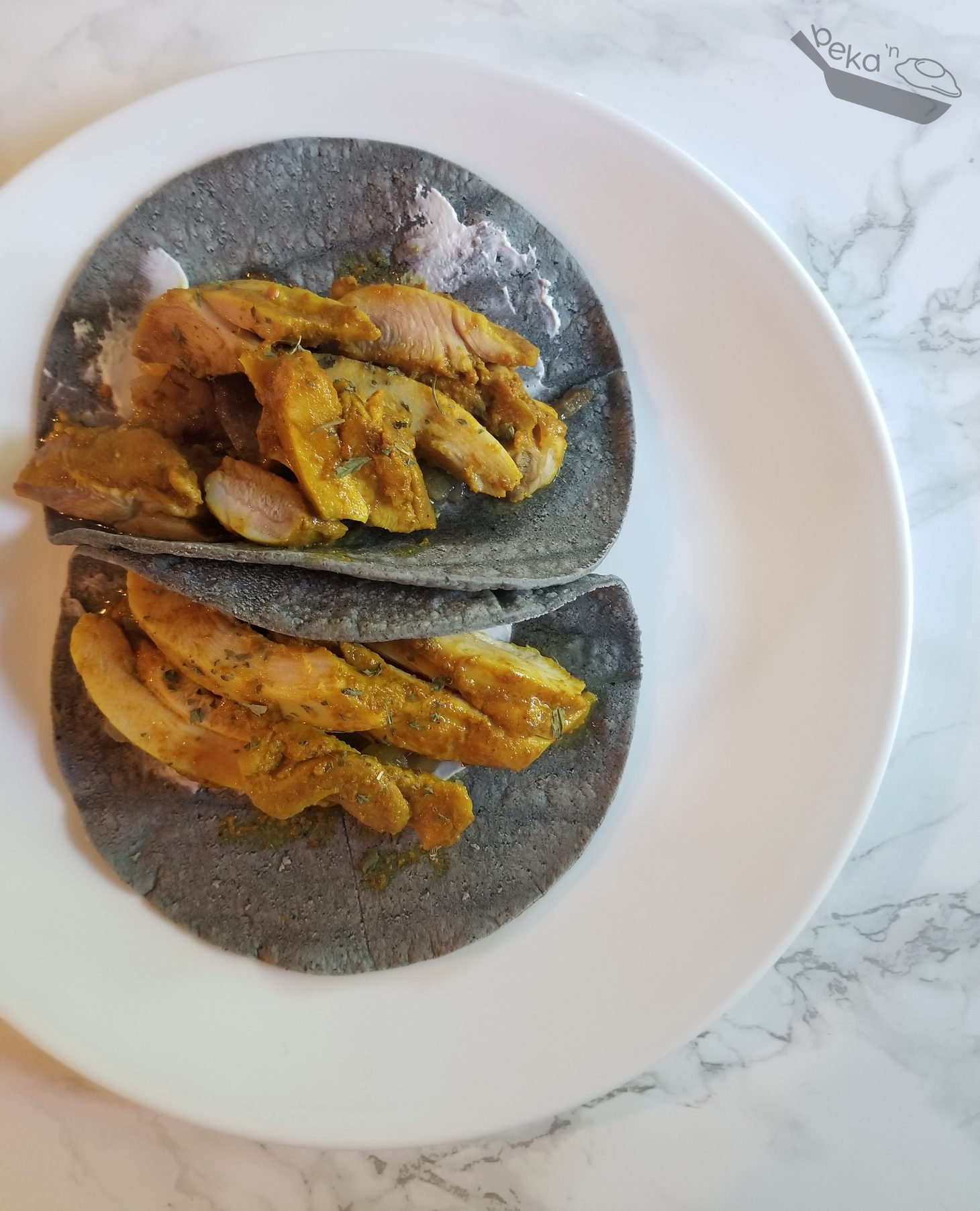 An overhead shot of Tandoori chicken in blue corn tortillas on a white plate. The plate is on a white marble background.