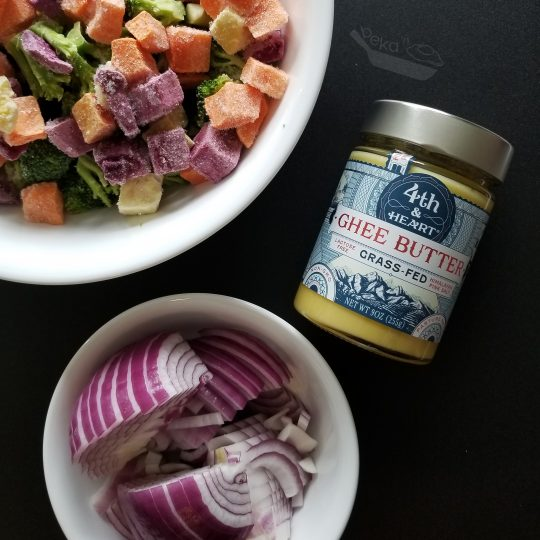 A beautiful overhead shot on a black background with the ingredients for this recipe. A large white bowl with frozen broccoli and sweet potato, a small white bowl with sliced red onion, and a jar of 4th and Heart brand ghee.