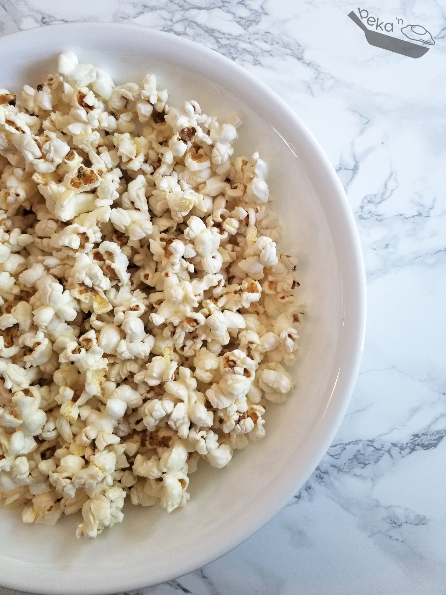An overhead image of homemade popcorn in a large white bowl on a white marble background.